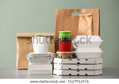 Different packages on table against color background. Food delivery service Сток-фото ©