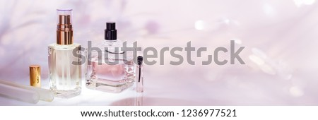 Different perfume bottles and sampler on a pink floral background. Perfumery collection, cosmetics Banner #1236977521