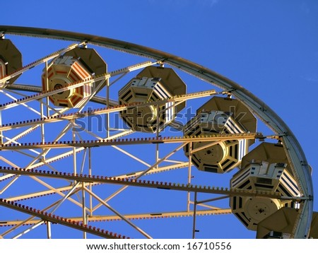 Different perspective on ferris wheel. Ferris wheel is isolated against beautiful blue sky.