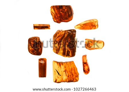 different pieces of amber on a white background. Amber of various colors and structure and shapes. Transparent and opaque pieces of amber. Natural amber #1027266463