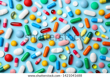 Photo of  Different pills on color background, flat lay