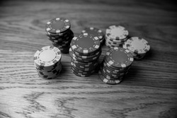 Different poker chips on table at casino. Poker chips. Poker chips on wooden desk, gambling concept. black and white photo