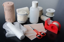 Different rolls of medical bandages and care equipment on a black background