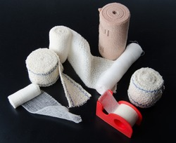 Different rolls of medical bandages and sticking plaster on a black background