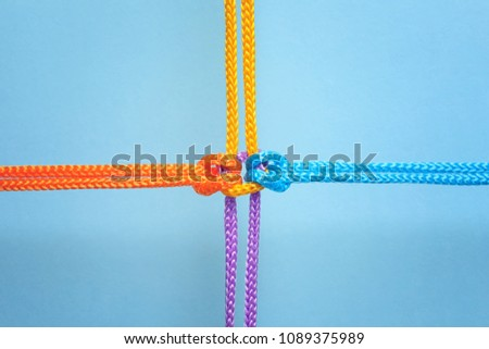 Different ropes tied together with knot on color background. Unity concept #1089375989