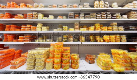 Different salads in plastic containers on shelves in large store