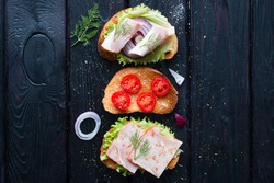 Different sandwiches with meat and vegetables on a black background