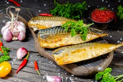 different sea smoked river fish lies on a screw-up rustk on a chopping board and a table, the ropes, slices of lemon and lime are cut whole round, around, with greens light, top side view, around
