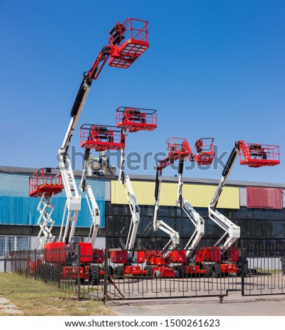 Different self propelled articulated boom lifts and one scissor lift red with white colors on a background of industrial building and clear sky