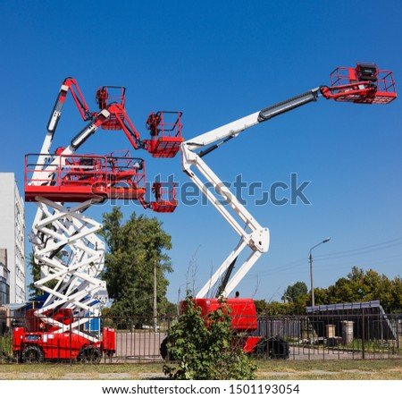 Different self propelled articulated boom lifts and one scissor lift red with white colors on a background of trees and clear sky