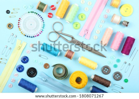 different sewing accessories on the table. Threads, needles, pins, fabric and sewing scissors close up  Foto stock ©