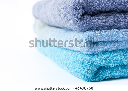 Different shades of blue towels stacked on each other on a white background