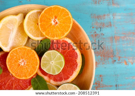 Different sliced juicy citrus fruits in bowl on blue wooden table #208512391