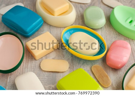 Different soaps in different soap dishes. A lot of solid soap for hygiene and cleanliness. Colorful soap and remnants are scattered on the table.