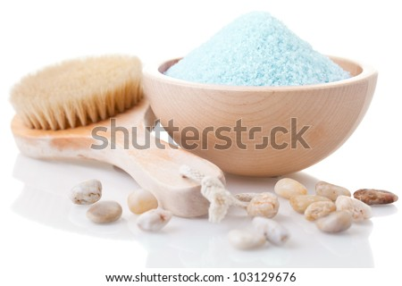 Different spa utensils with bathing salt in bowl on white background