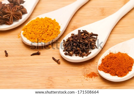 Different spices on spoons in light wooden table background