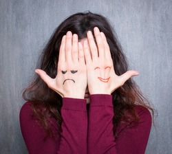 Different states of mood, woman covering her face with hands with drawn happy and sad