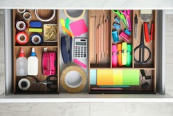 Different stationery in open desk drawer, top view