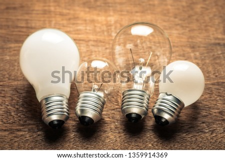 Different style and size of light bulbs on wood table, business solutions concept #1359914369