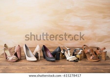 Different style woman's high heels on wooden floor #615278417