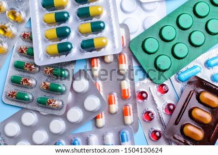 Different tablets, pills in foil blister packs, medications drugs on blue background ストックフォト ©