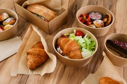 Different takeout food on wooden kitchen table. Italian panini sandwich, french croissant with salmon, strawberry pancakes and chocolate cheesecake. Close up, top view, pov, copy space, background.