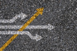 Different thinking and Business and technology disruption concept , Yellow arrow cross direction with white arrow on road asphalt.