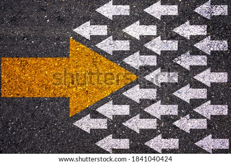Different thinking and Business and technology disruption concept. Yellow big arrow opposite  direction with white arrow on road asphalt.  Stockfoto ©