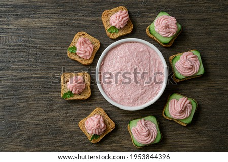 Different toasts with tarama around a white bowl with taramasalata on a dark wooden table, top view Stok fotoğraf ©