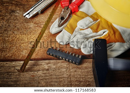 Different tools and gloves on  wooden background.