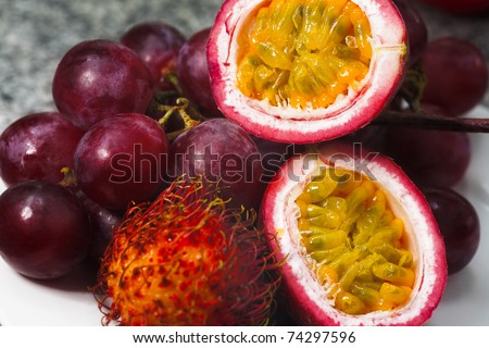 different tropical fruits - passion fruit, rambutan and grape