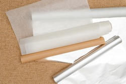 Different type of paper for baking needs. Parchment paper, foil, wax paper close up on rustic background, flat lay