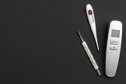 Different type of thermometers on grey background. Infrared, electronic and mercury thermometers. Top view. Space for text.