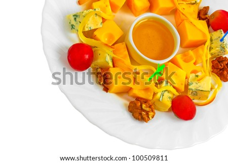 Different types cheese appetizer with honey, nuts and grapes on a plate isolated on white background (clipping path)