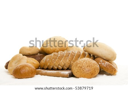 different types of bread on a wooden board sprinkled with flour