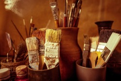 Different types of brushes for oil and acrylic painting, palette knives stand upright in clay vases in the artist's studio.