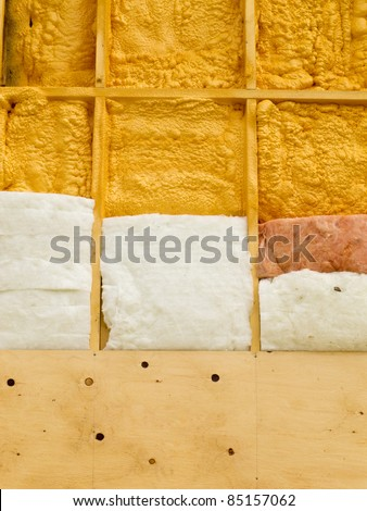 Different types of building insulation: polyurethane spray foam and fiberglass mats.