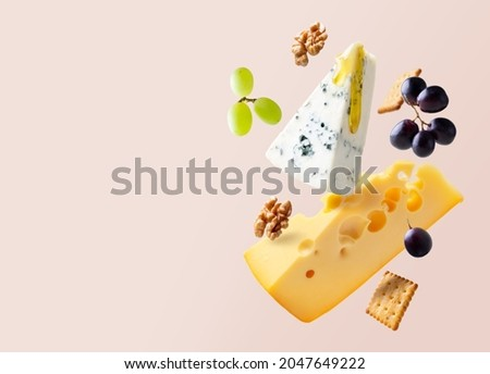 Different types of cheese are flying or falling in the air. Levitation concept. Cheeses mix maasdam, dor blue, camembert, brie and grapes, walnuts, galeta. Isolated. Copy space. Stockfoto ©