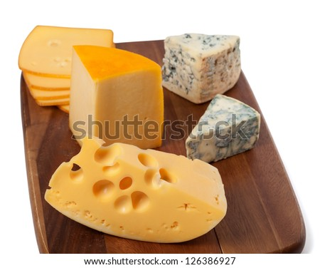 Different types of cheese on wooden kitchen board