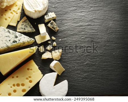 Shutterstock Different types of cheeses on black board.