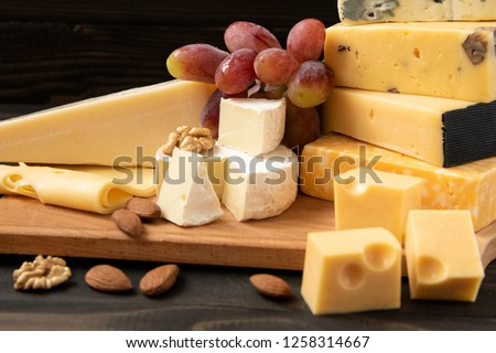 Different types of cheeses. slices of cheese brie or camembert with parmesan, cheddar, gouda, roquefort  and other with nuts on wooden board on dark background