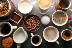 Different types of coffee in cups on dark table, top view