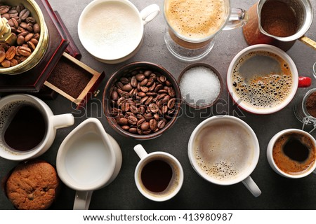 Different types of coffee in cups on dark table, top view #413980987