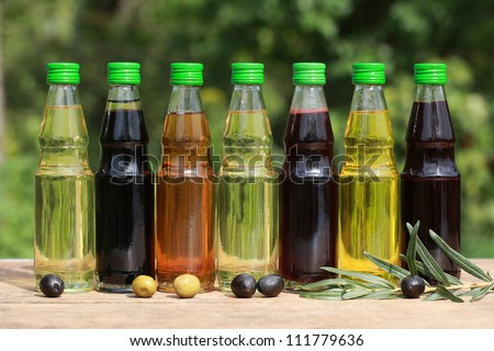 Different types of cooking oil in small bottles on a wooden table
