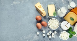 Different types of dairy products on grey background. Top view with copy space