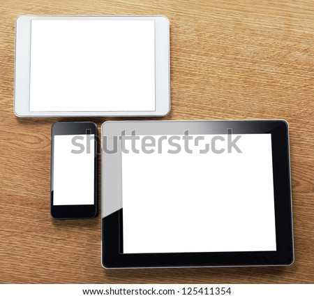 different types of digital tablet and smart phone on a desktop. a mobile phone and a tablets on a table