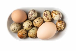 Different types of eggs in bowl isolated on white. Chicken, guinea fowl and quail eggs on white plate. Top view.
