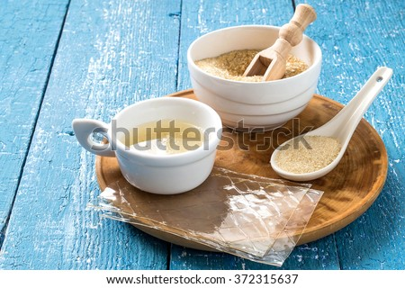 Different types of gelatin (powder, granules, sheets and gelatin solution) on a blue wooden table