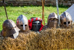 Different types of knight's helmets standing in a row on a straw bale. Medieval knight tournament background