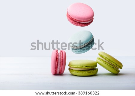 Different types of macaroons in motion falling on a white wooden background